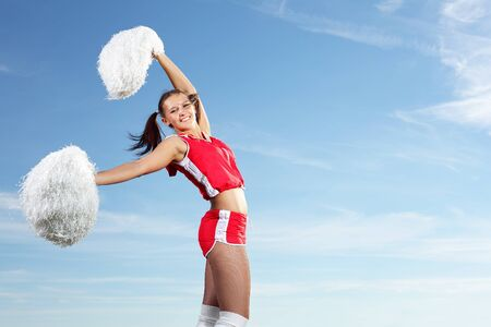 cheerleading squad: Young beautiful female cheerleader in uniform jumping high