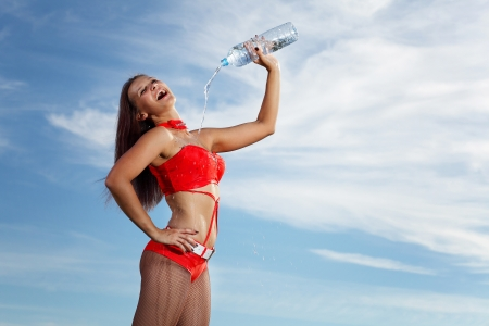 Young female sport girl in red uniform with a bottle of water Stock Photo - 16352672