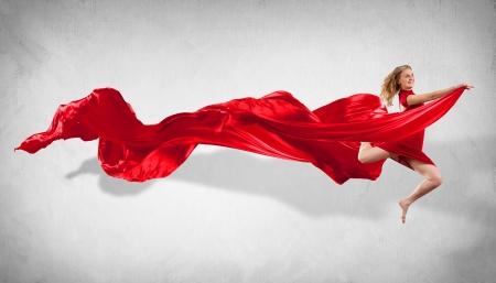 Portrait d'une jeune femme dansant avec un tissu rouge