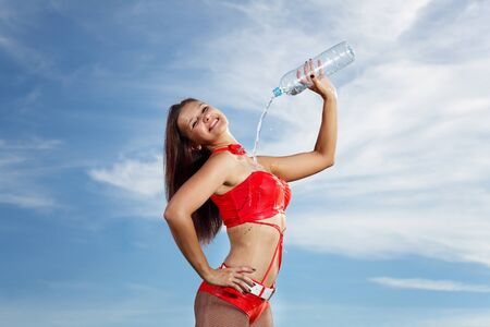 Young female sport girl in red uniform with a bottle of water Stock Photo - 16352648