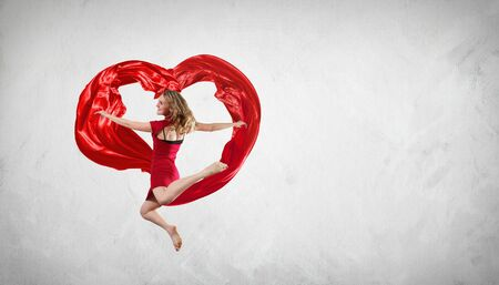 Young woman dancing with red fabric in studio and heart symbol Stock Photo - 16350871