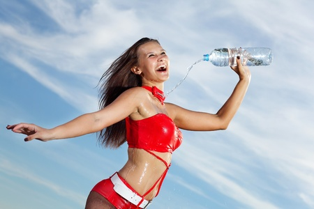 Young female sport girl in red uniform with a bottle of water Stock Photo - 16353014