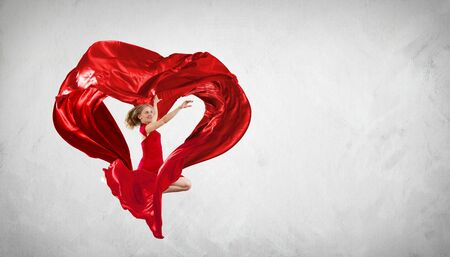 Young woman dancing with red fabric in studio and heart symbol Stock Photo - 16350841