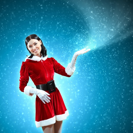 Portrait of beautiful girl wearing santa claus clothes on red background Stock Photo