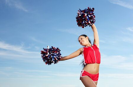 Young beautiful female cheerleader in uniform jumping high Stock Photo - 16490467