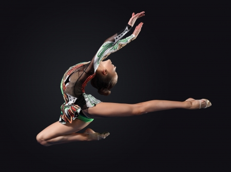 ballet dancing: Young cute woman in gymnast suit show athletic skill on black background