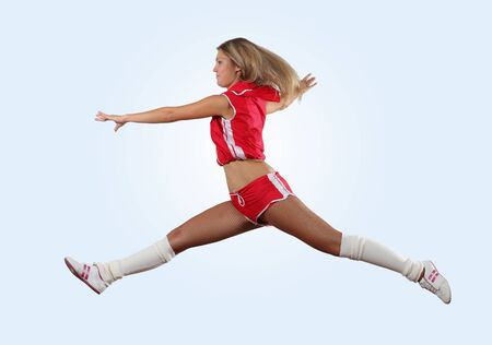 Uniformed cheerleader jumps high in the air isolated on white  photo
