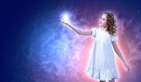 Little girl with magic lights and shining around photo