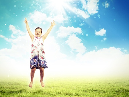 Photo of little girl jumping and raising hands against nature background