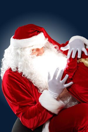 Santa Claus with his magic gift red bag full of presents photo