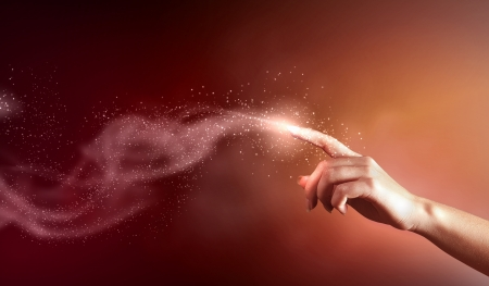 creative pictures: magical hand conceptual image with sparkles on colour background