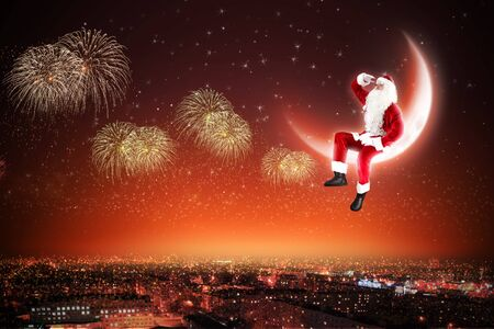 Santa Claus on the moon above a city at night Stock Photo - 16548513