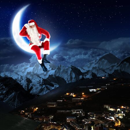 a santa claus sitting on the moon with a city and mountains below Stock Photo - 16548517