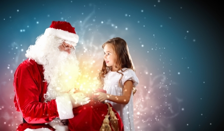 Portrait of Santa Claus with a little girl looking at a gift photo