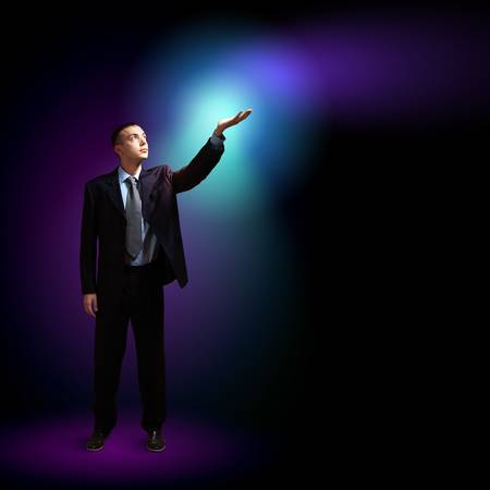 Young successful businessman holding a shining light in his hand as a symbol of success and advancement  Stock Photo - 16548887
