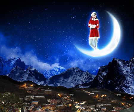 a santa claus sitting on the moon with a city and mountains below Stock Photo - 16548516