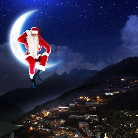 a santa claus sitting on the moon with a city and mountains below Stock Photo - 16548515