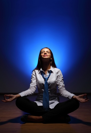 Young business woman sitting in asana lotus and meditating Stock Photo - 16548552