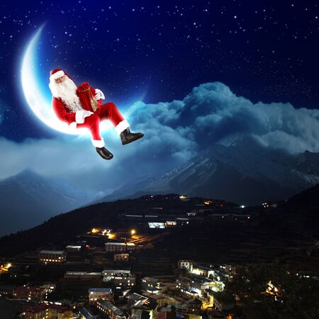 a santa claus sitting on the moon with a city and mountains below Stock Photo - 16548472