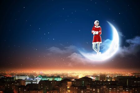 Santa Claus girl on the moon above a city at night Stock Photo - 16548807
