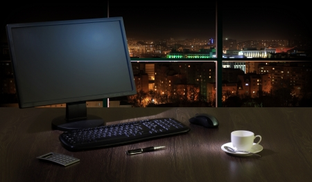 Work place in the office at night with a city view from window Stock Photo - 16524787