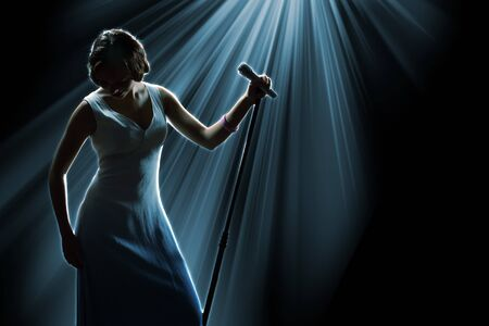 singer silhouette: Female singer on the stage holding a microphone