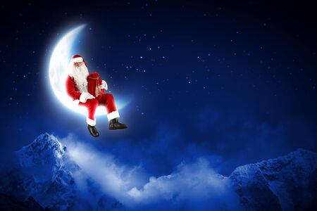 a Santa Claus sitting on shiny moon above winter forest Stock Photo - 16548833