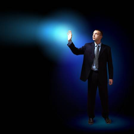 Young successful businessman holding a shining light in his hand as a symbol of success and advancement Stock Photo - 16548841