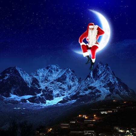 a santa claus sitting on the moon with a city and mountains below Stock Photo - 16548518