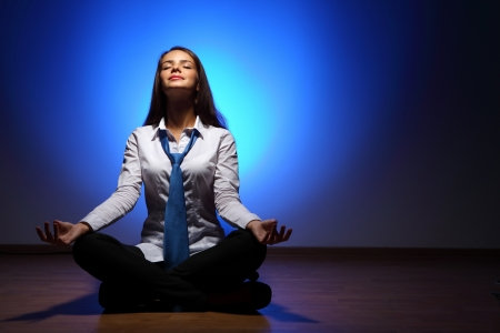 Young business woman sitting in asana lotus and meditating photo