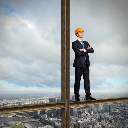 Businessman standing in suit on the construction site photo