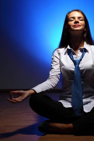 Young business woman sitting in asana lotus and meditating Stock Photo - 16577883
