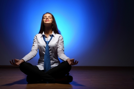 Young business woman sitting in asana lotus and meditating Stock Photo - 16577879