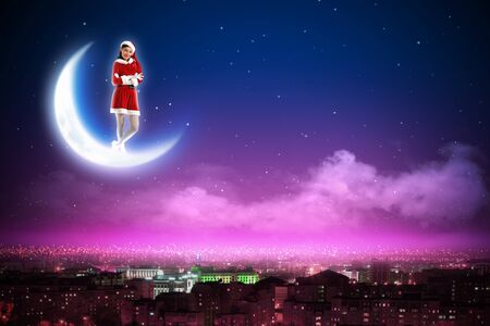 Santa Claus girl on the moon above a city at night Stock Photo - 16589860