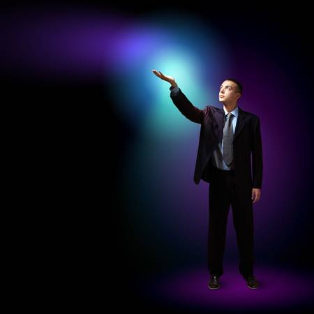 Young successful businessman holding a shining light in his hand as a symbol of success and advancement Stock Photo - 16589646