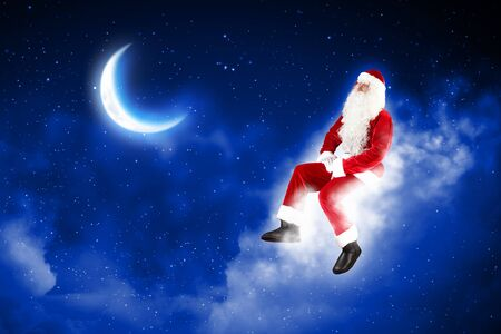 Photo of Santa Claus sitting on shiny moon above winter forest Stock Photo - 16589704