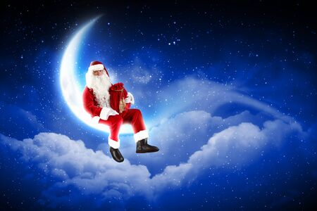 Photo of Santa Claus sitting on shiny moon above winter forest Stock Photo - 16589778