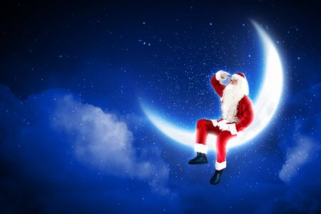 Photo of Santa Claus sitting on shiny moon above winter forest Stock Photo - 16589018