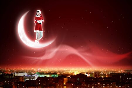 Santa Claus girl on the moon above a city at night photo