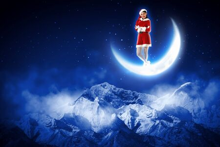 christmasbackground: Santa girl standing on shiny moon above winter forest