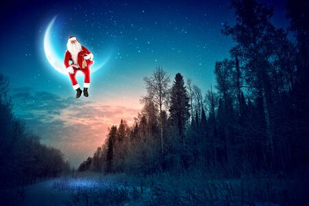Santa Claus sitting on shiny moon above winter forest photo