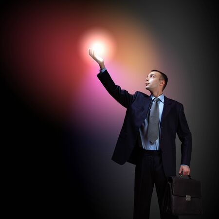 Young successful businessman holding a shining light in his hand as a symbol of success and advancement  Stock Photo - 16616593