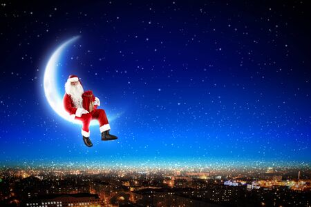 Santa Claus on the moon above a city at night Stock Photo - 16616668