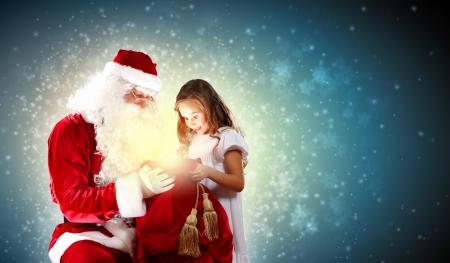 贈り物を見て女の子とサンタ クロースの肖像