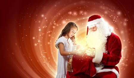 Portrait of Santa Claus with a little girl looking at a gift Stock Photo - 16655175