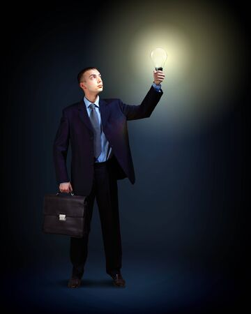 Young successful businessman holding a shining light in his hand as a symbol of success and advancement  Stock Photo - 16616389