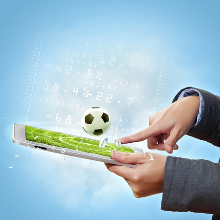 games hand: Modern wireless technology illustration with a computer device and football ball