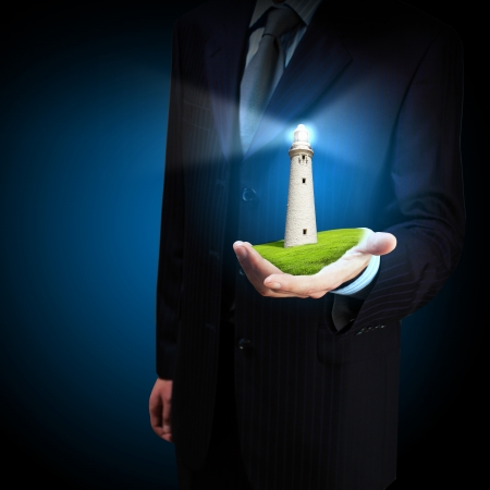 Business man and a lighthouse shining in darkness photo