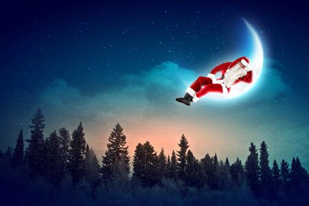 Santa Claus sitting on shiny moon above winter forest Stock Photo