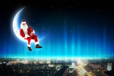 Santa Claus on the moon above a city at night Stock Photo - 16690314